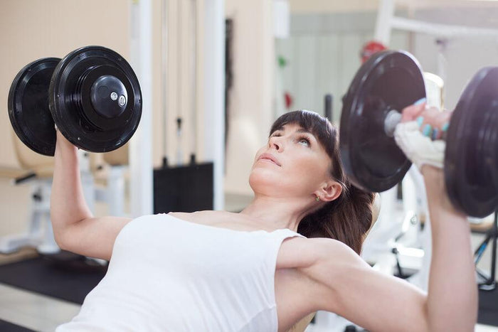 women lifts weights on a bench press