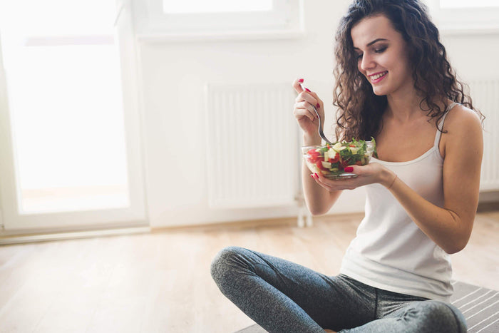 woman eats salad while sitting on a wooden floor