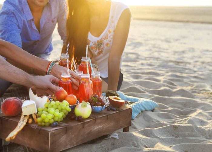 people share an assortment of juice and fruit on a beach
