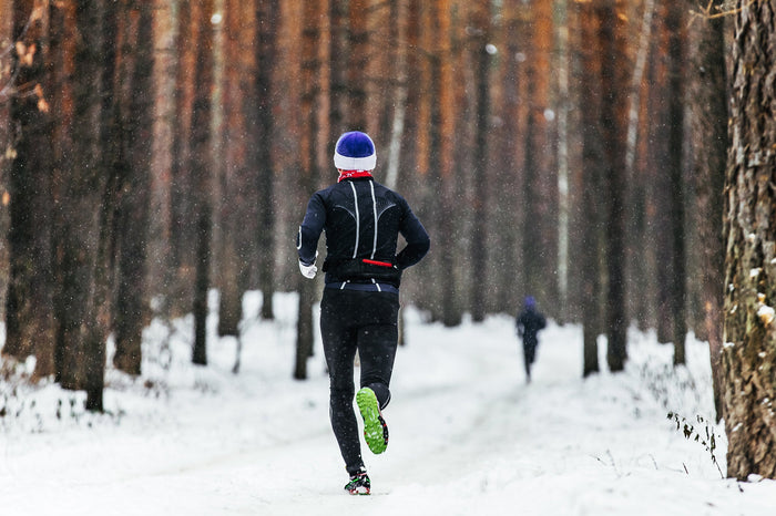 man runs a snow covered trail in the woods