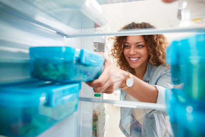 how-to-create-healthy-habits-meal-planning-woman-looking-in-refrigerator-getting-out-food-eating-healthy
