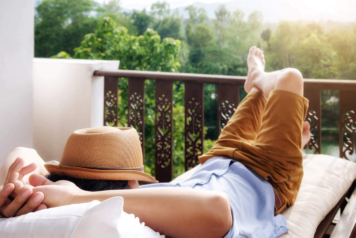 man lays with hat over his face on a patio
