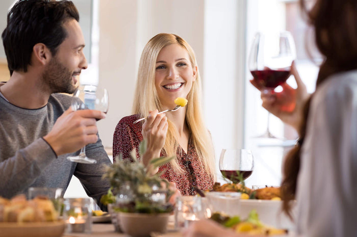 friends smile while drinking wine at dinner together