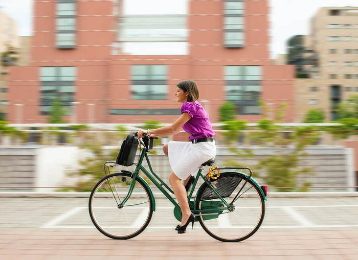 women riding into work on a bike
