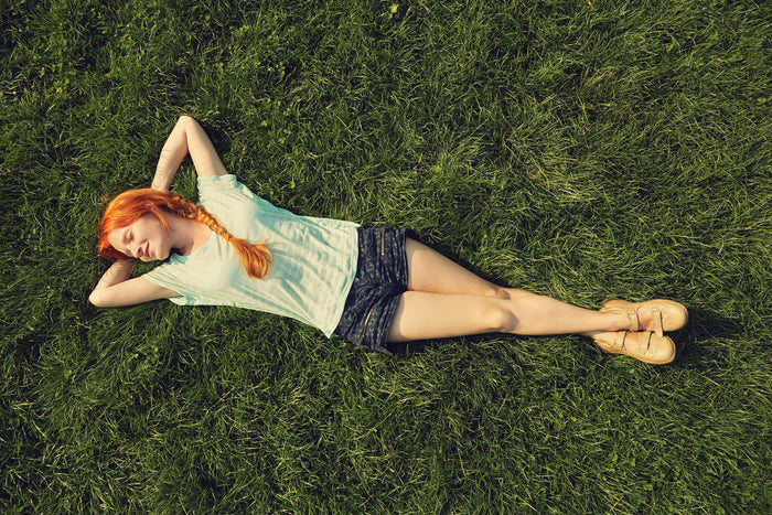 women lays in the grass with her hands behind her head