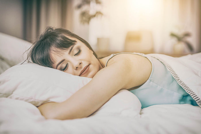 women sleeps with a pillow in her bed