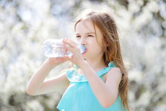 little girl drinks from a water bottle