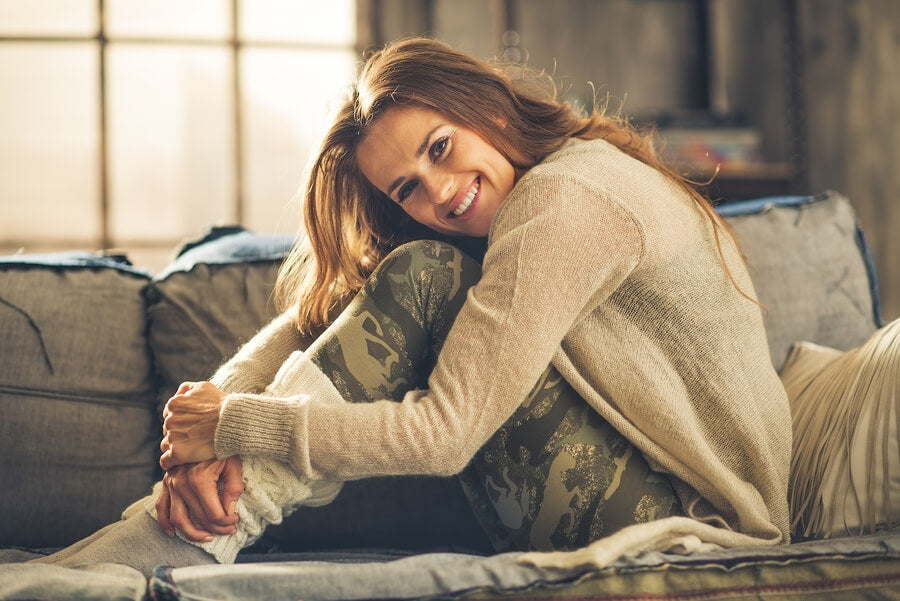 An elegant brunette woman is smiling hugging her knees. Wearing comfortable casual clothing leggings and a cardigan she is relaxing on a loft sofa. Industrial chic ambiance and cozy atmosphere.