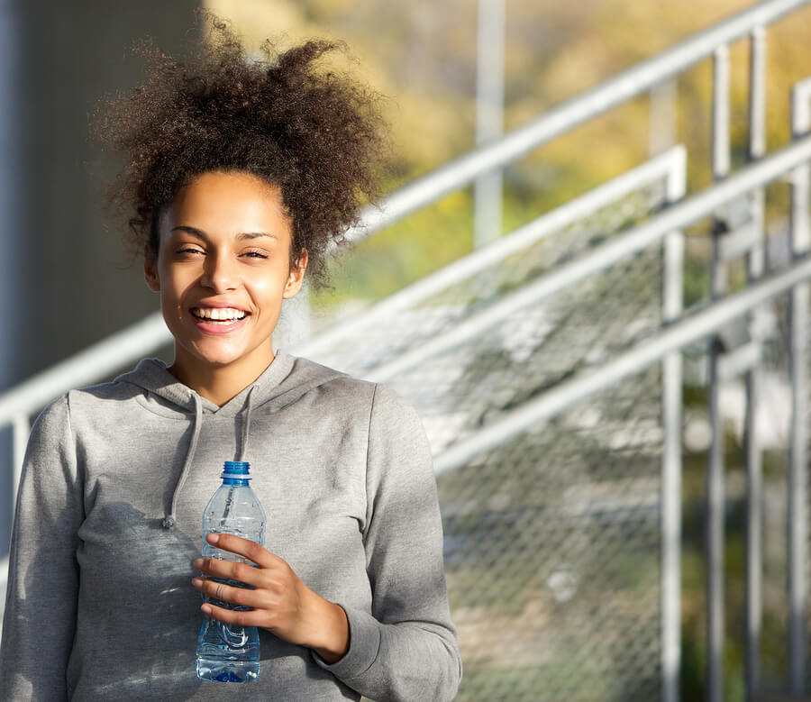 Close up portrait of a happy young woman smiling with water bottle