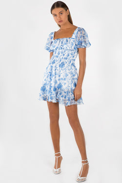 Model wears Alina mini dress with Puff sleeves and leg split in colour blue floral