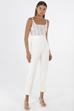 Model wears Ariella lace pantsuit with belt in colour ivory