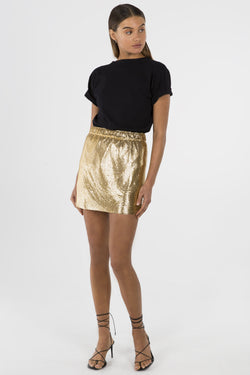 Model wears Astelle mini skirt in colour gold