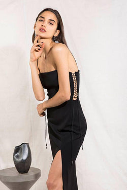 Model wears Desiree midi dress with leg slit in colour black