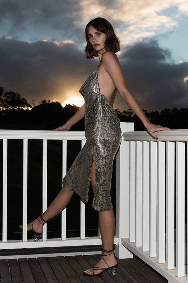 Model wears Eryn glo mesh midi backless halter neck dress in colour snakeskin