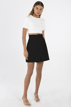 Model wears Fiorella mini skirt in colour black