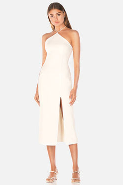 Model wears Genevieve midi halter neck leg slit dress in colour ivory