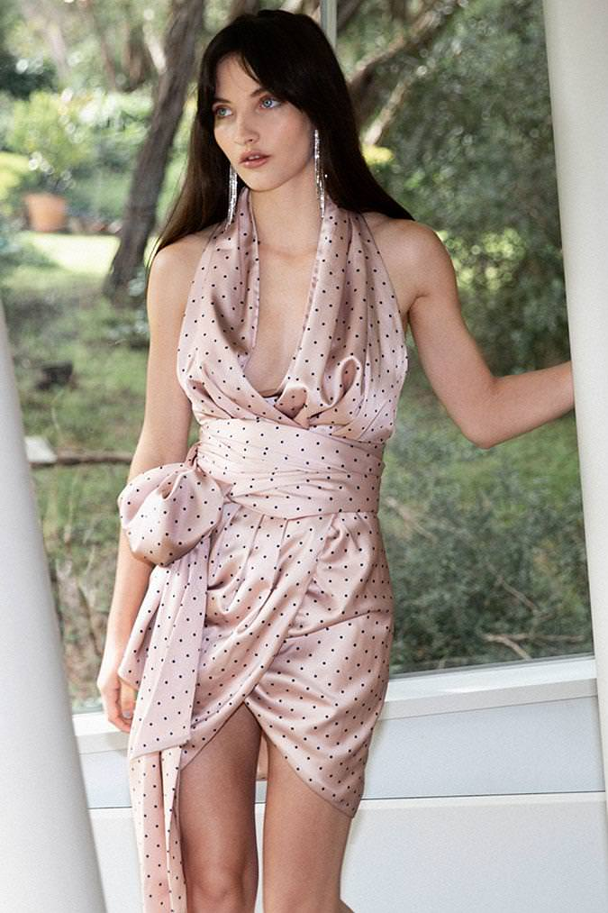 Model wearing Ceilla Mini wrap halter dress in blush navy polker dot