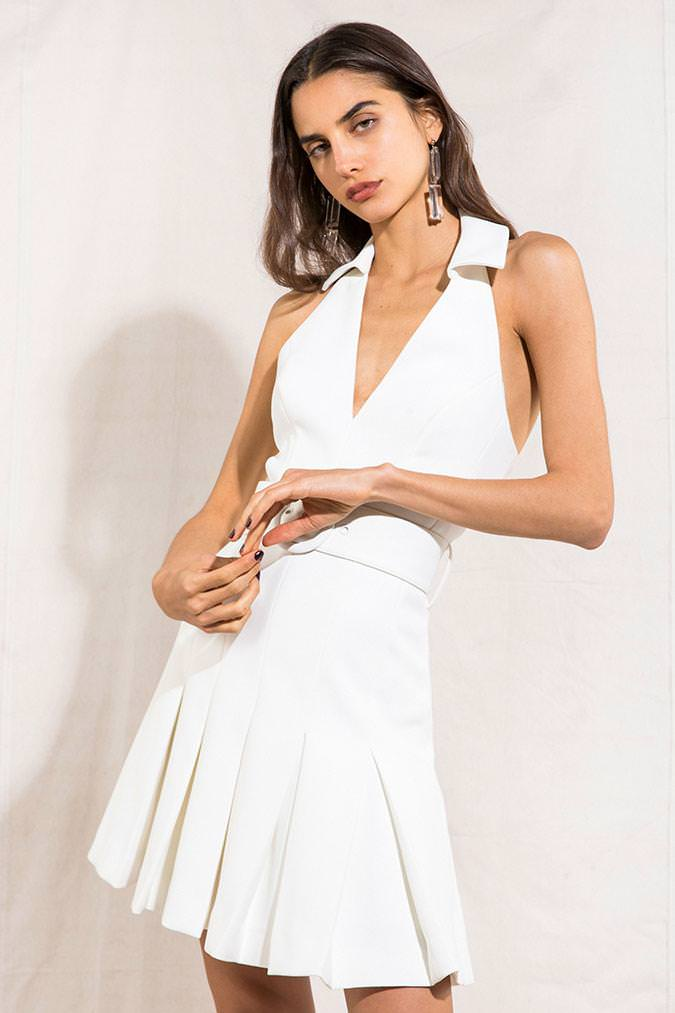 Model wearing Lucinda mini halter pleated dress in colour Ivory