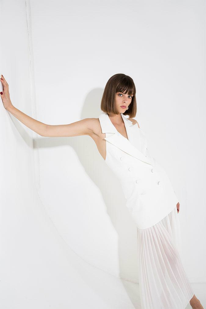 Model wears Sammiah Midi halter blazer dress in Ivory with sheer pleated skirt