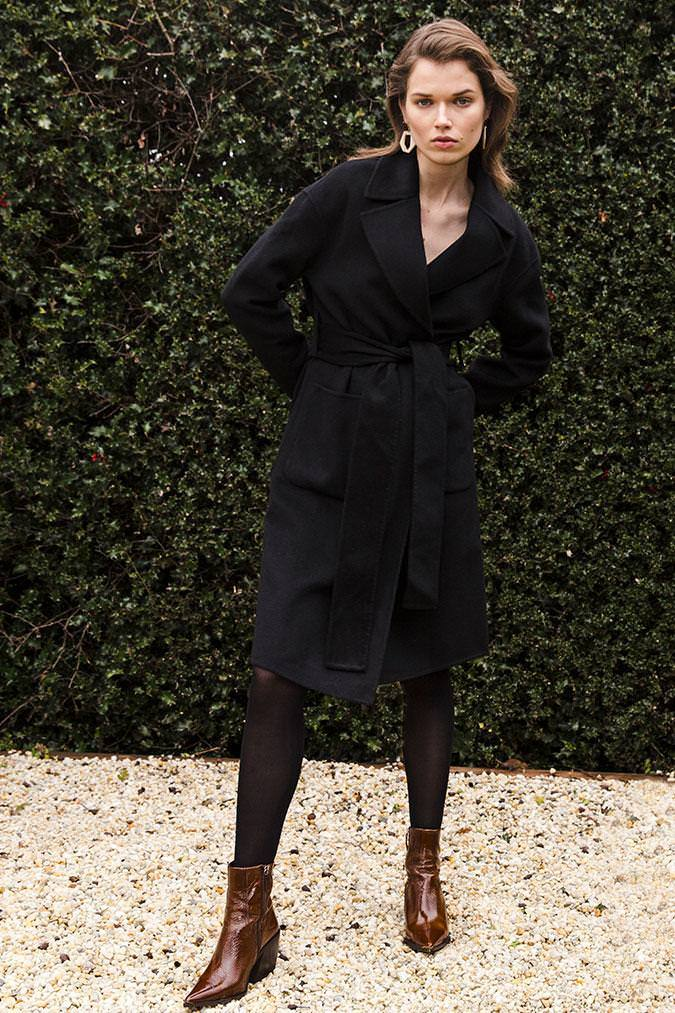 Model wears Haillie wool coat with oversized pockets in colour black