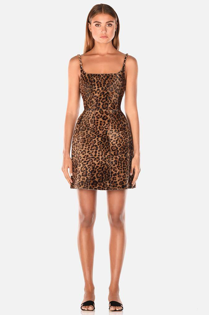 Model wears Kamille mini leather chain strap dress in colour leopard