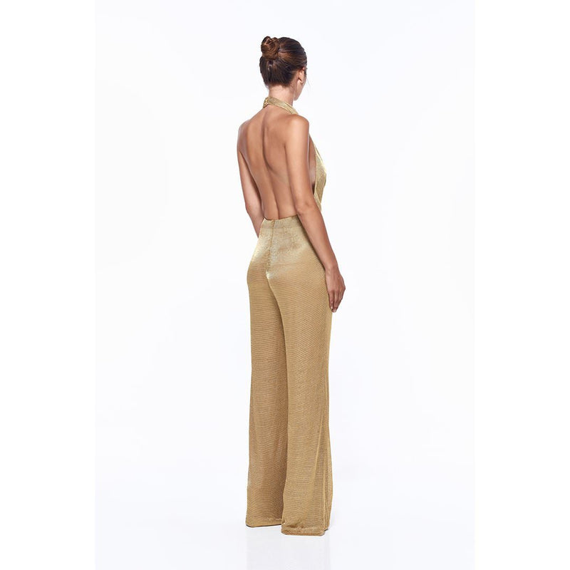 Model wears Olivia halter neck pantsuit in colour gold