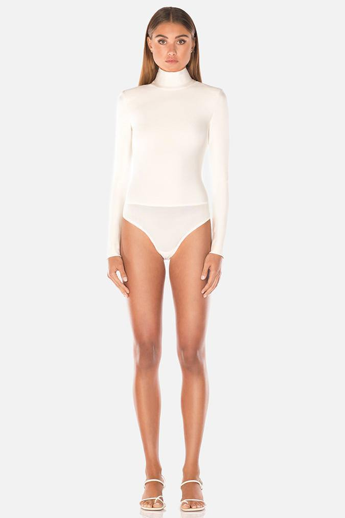 Model wears Petunia long sleeve bodysuit with high neck in colour ivory