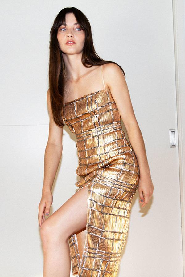 Model wears Yvette sequin midi dress with leg split in colour gold