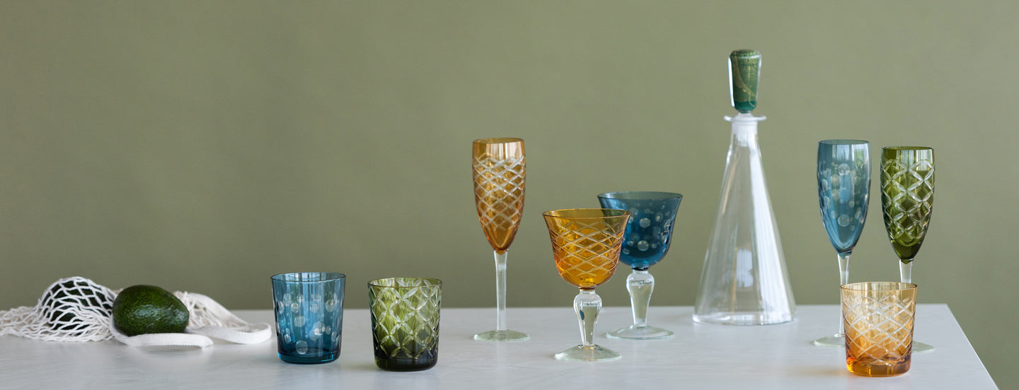colorful-glasses-wine-glass-decanter-champagne-glasses-and-net-with-fruits.