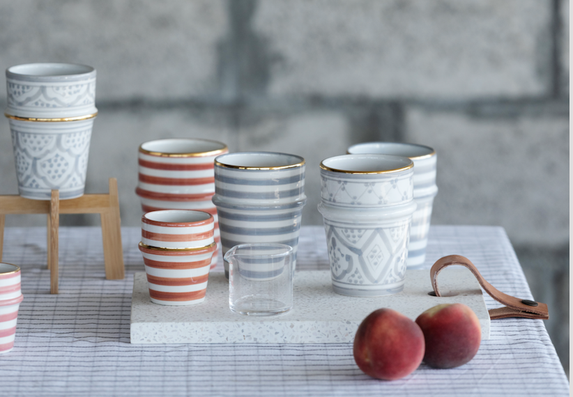 A Chabi Chic patterned glass cups set and orange & grey stripes sets placed in a table with small fruit