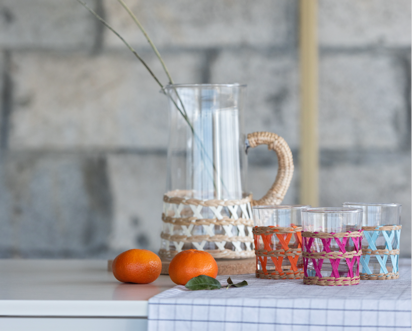 tumbler and reed set. glass jug and glasses with orange, pink and blue reed decor placed in the table with small orange