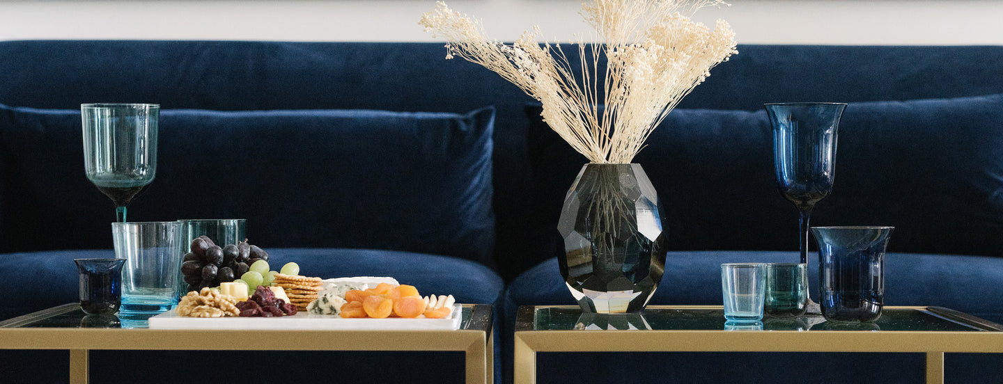 blue-velvet-couch-in-a-living-room-setting-with-glass-vases-cheeseboards-blue-glasses