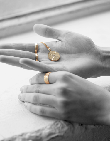 Black and white photo of hands holding gold medallion necklace by Bexon Jewelr