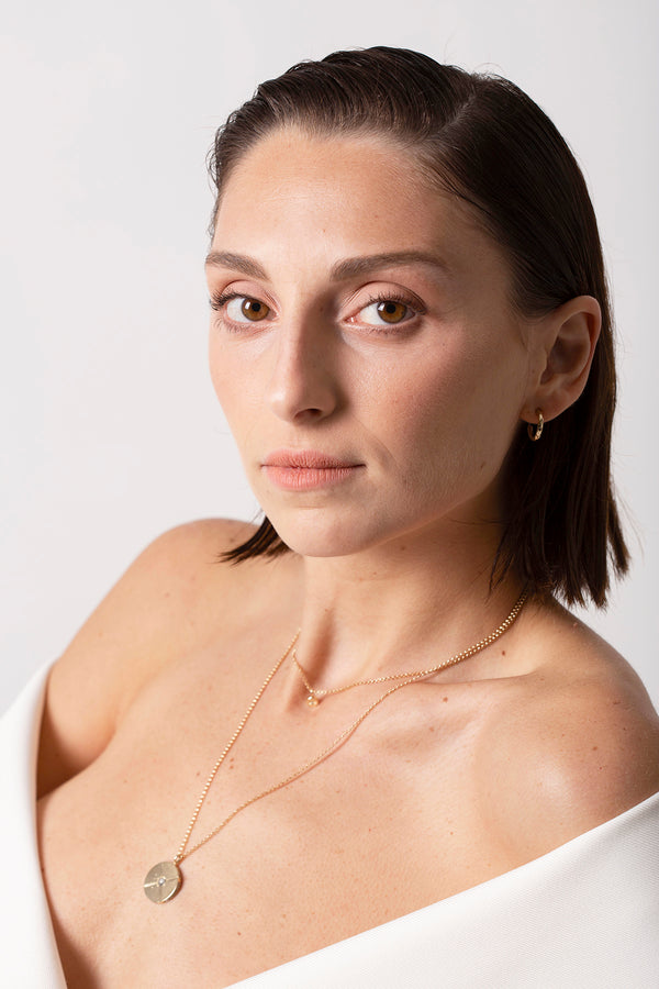 A model wears Bexon Jewelry Sole Medallion with pavé necklace, Stella necklace and Noa hoops, all in 14k yellow gold