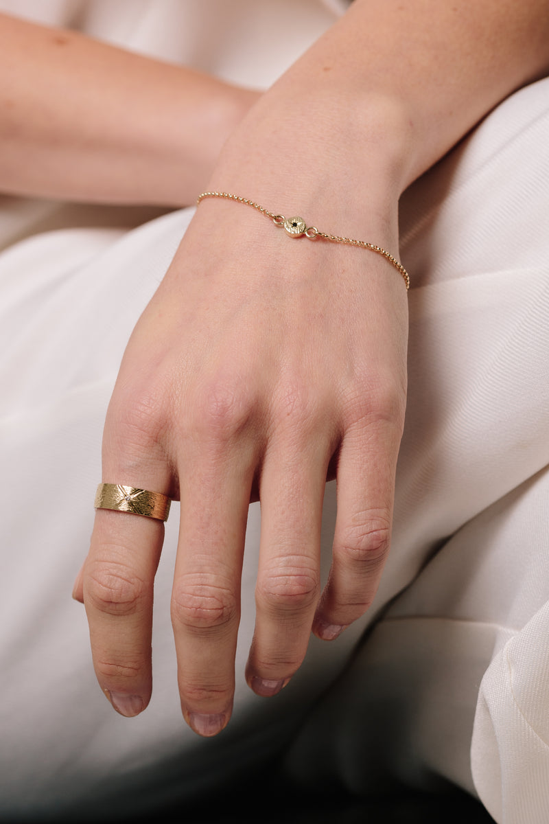 A model wears Bexon Fine Jewelry Regni wide cigar band ring in 14k recycled gold and flush set grey or black conflict-free diamond