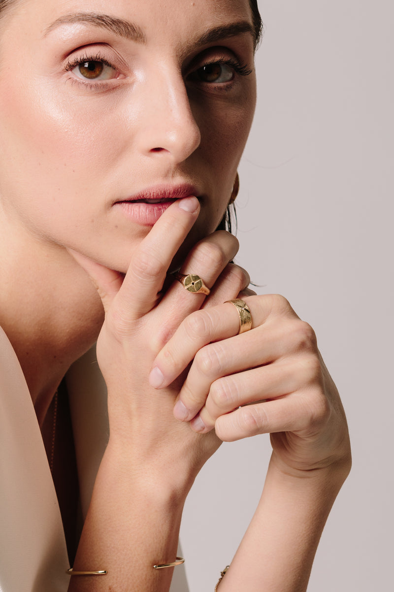 A model wears Bexon Fine Jewelry Opus round signet ring in 14k recycled gold and flush set grey or black conflict-free diamond