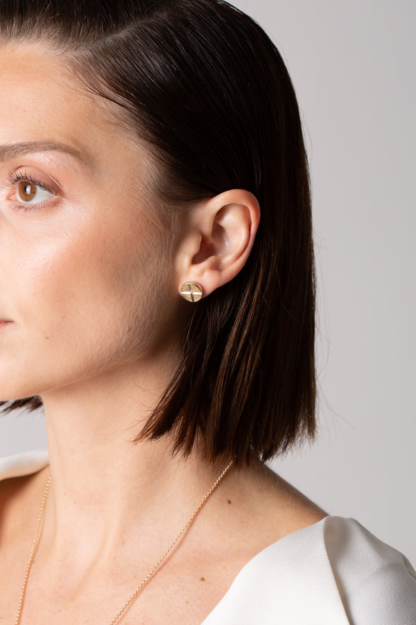 A model wears Bexon Fine Jewelry Maya Post earrings, 10 mm. button style posts in 14k recycled yellow gold with black or grey conflict free diamonds
