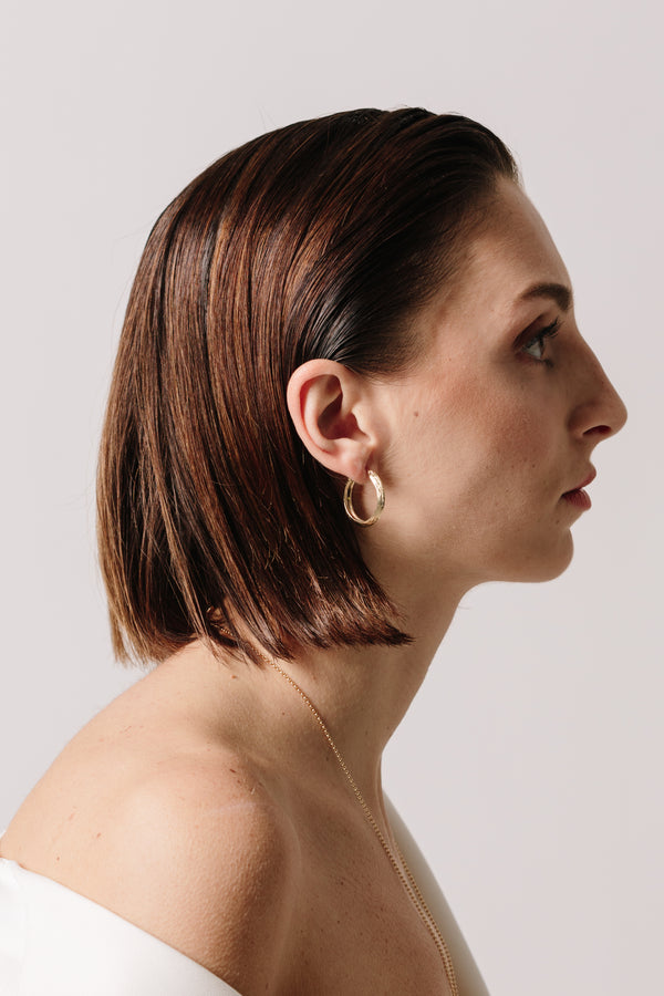 A profile view of a model wearing Bexon Fine Jewelry Gloria Hoop Earrings in 14k recycled yellow gold with hinge and catch closure
