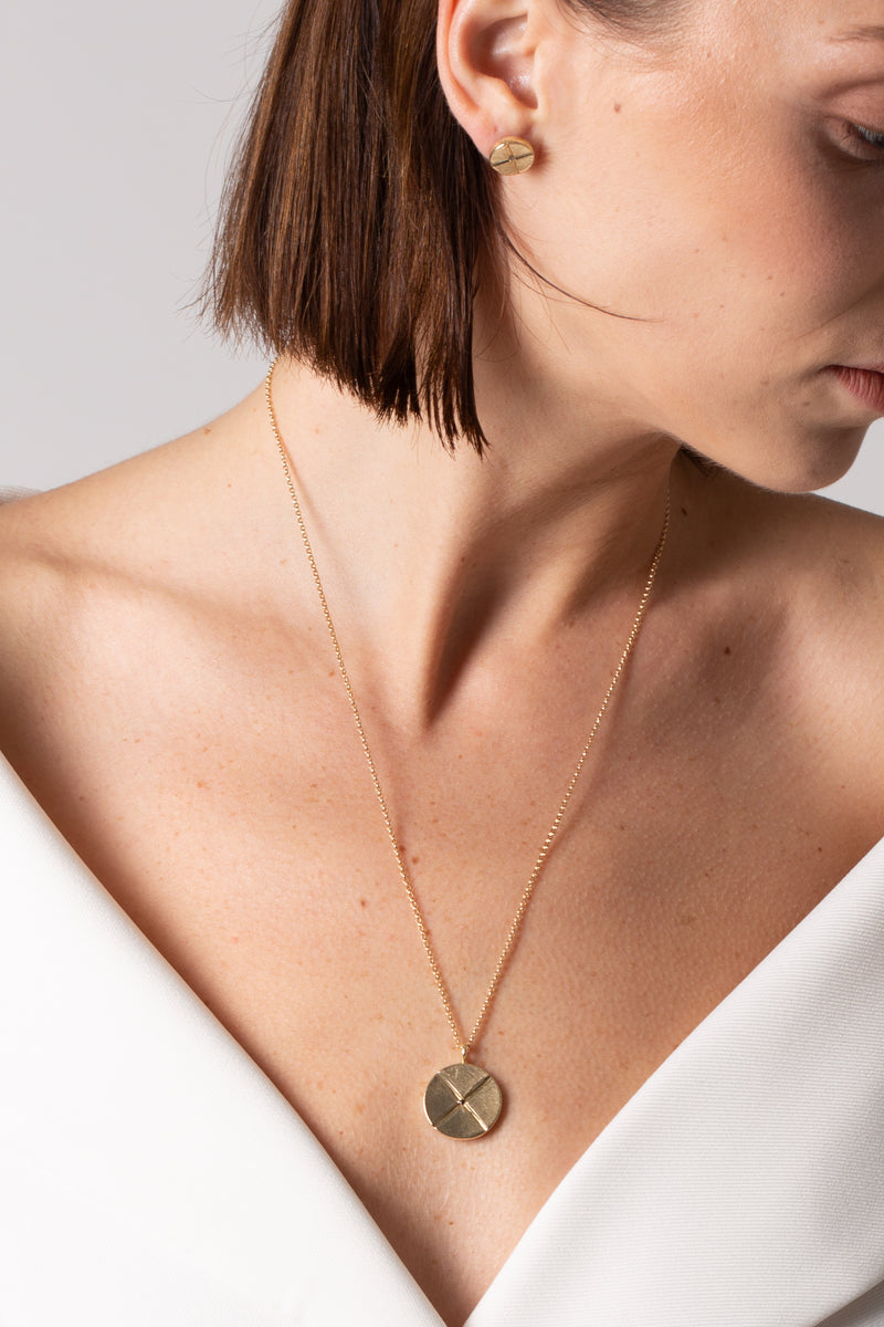 "A model wears Bexon Fine Jewelry Sole Medallion pendant necklace, 20 mm. diameter on 20"" rolo chain, 14k recycled yellow gold and conflict free black or grey diamonds"