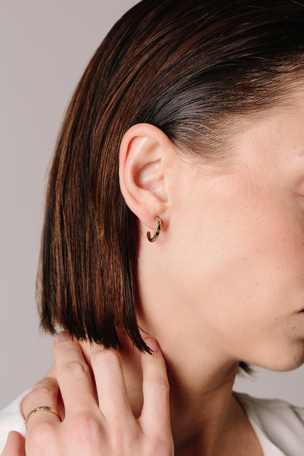 A model wears Bexon Fine Jewelry Noa hoop earrings in 14k recycled yellow gold and black or grey conflict free diamonds