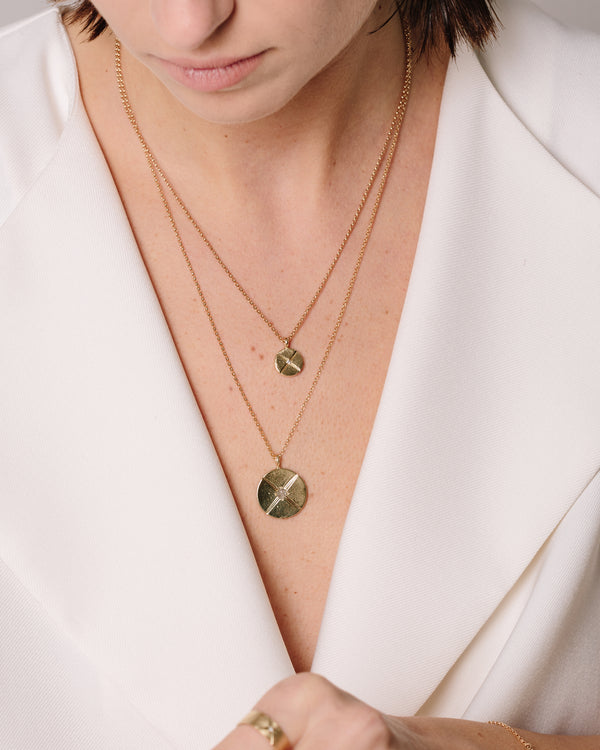 A model wears the Bexon Fine Jewelry Maya Necklace,10 mm. pendant in  14k recycled yellow gold with black or grey conflict free diamond