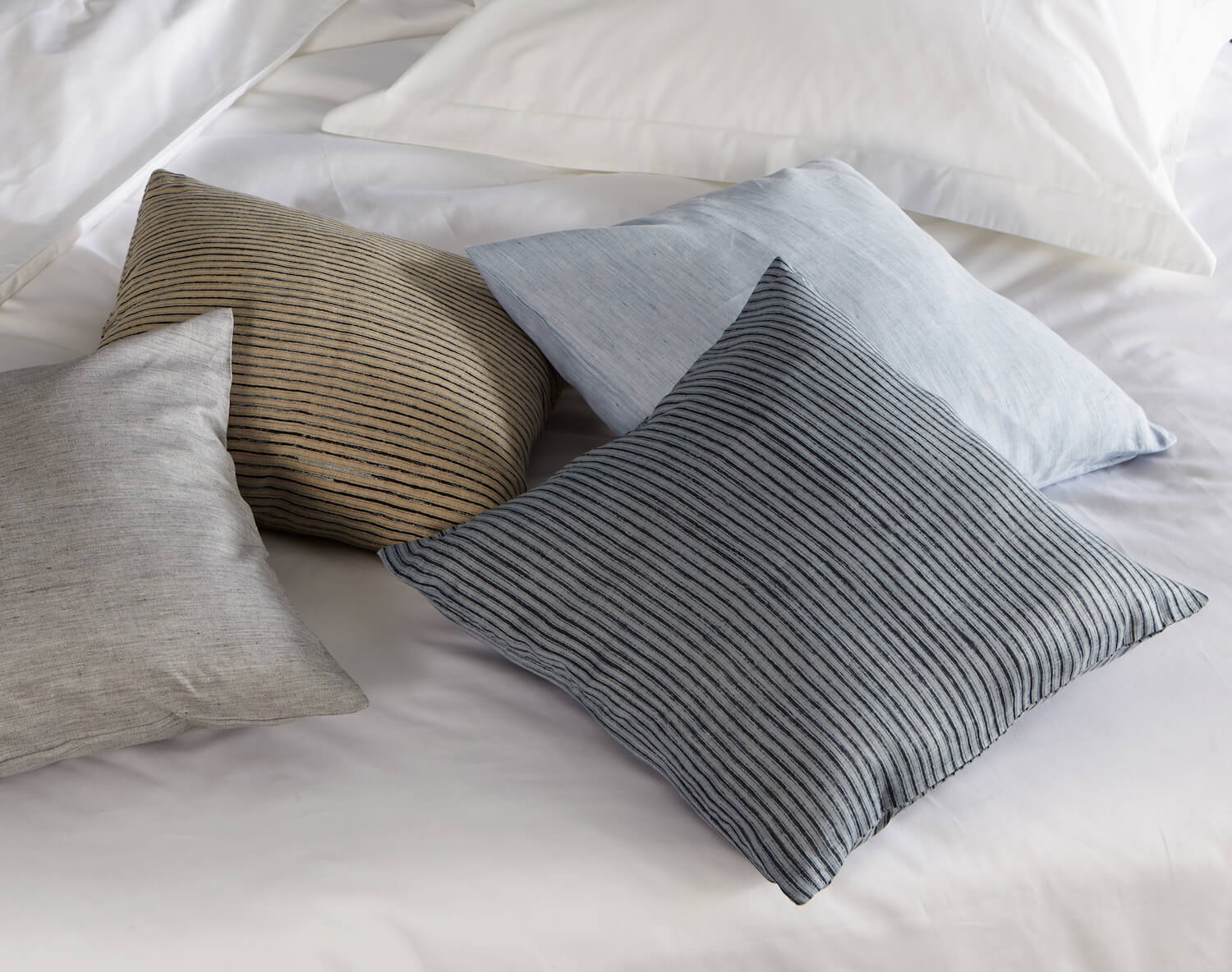 four scatter cushions in different colours on white duvet cover