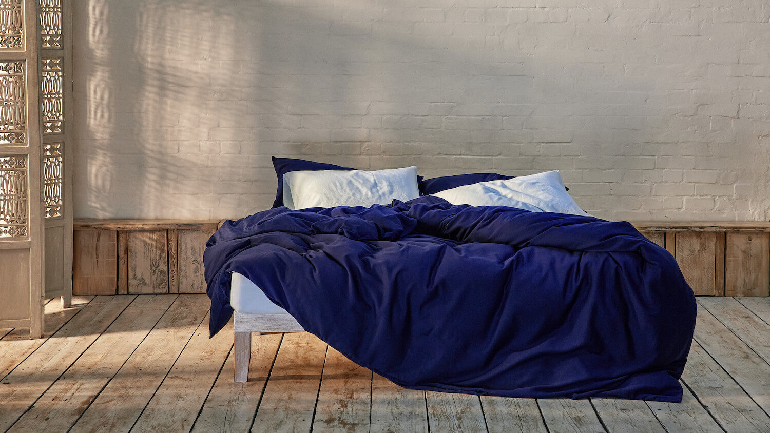 navy blue and baby blue bedding mix and match on bed in a modern room