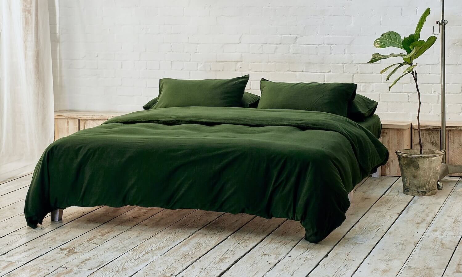 dark green duvet cover, two pillowcases, and bottom sheet on double bed in apartment with plant and wooden flooring