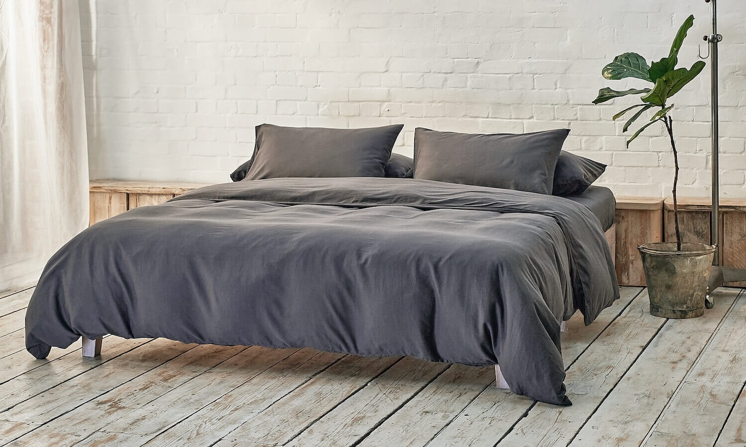 dark grey duvet cover, two pillowcases, and bottom sheet on double bed in apartment with plant and wooden flooring