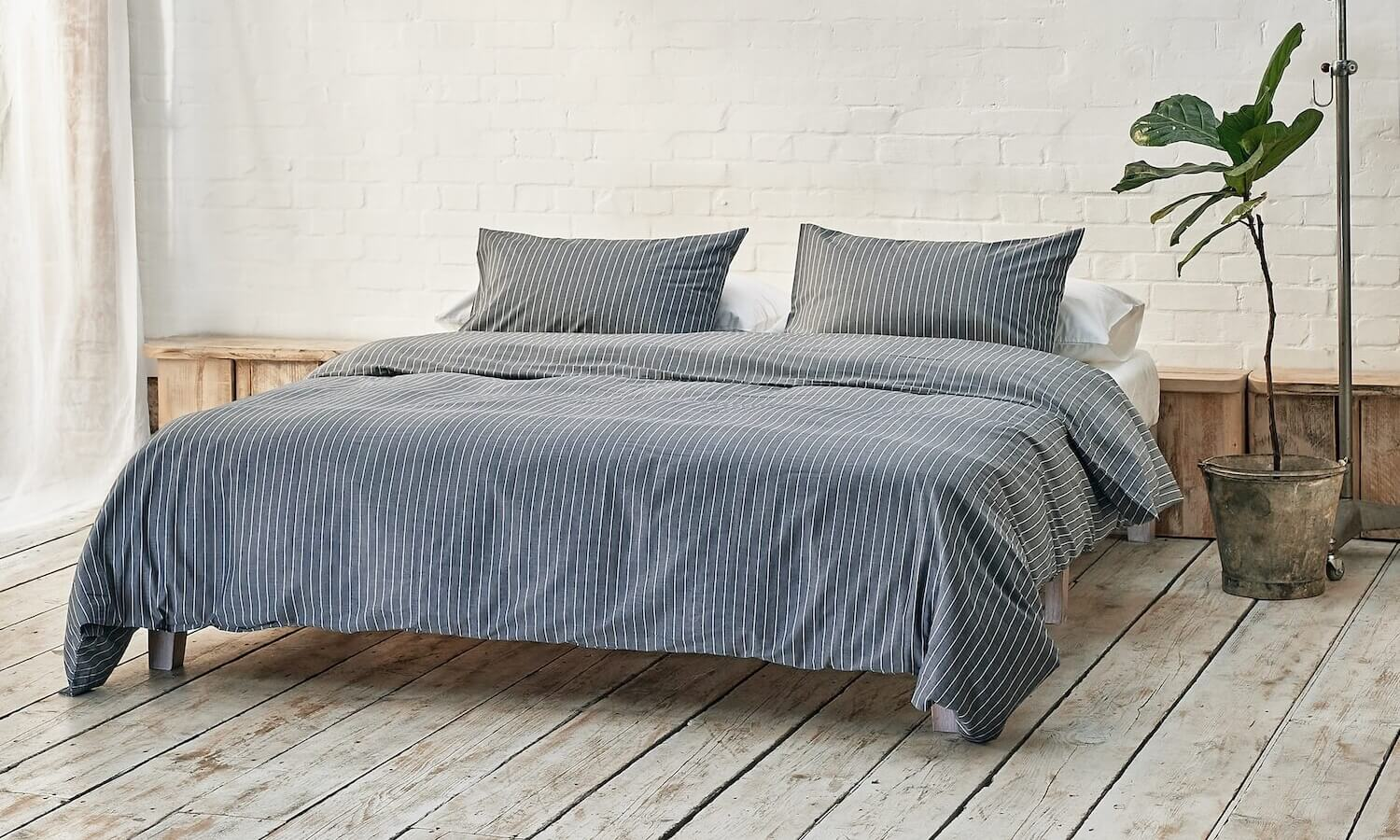 navy and white striped bedding on bed in a modern room