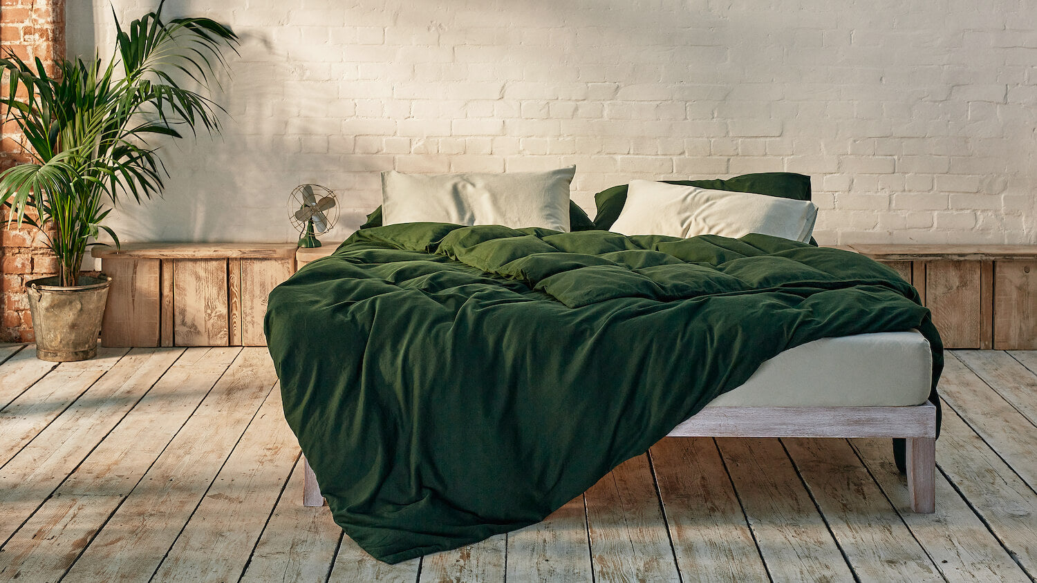 sage green and dark green bedding mix and match on bed in a modern room
