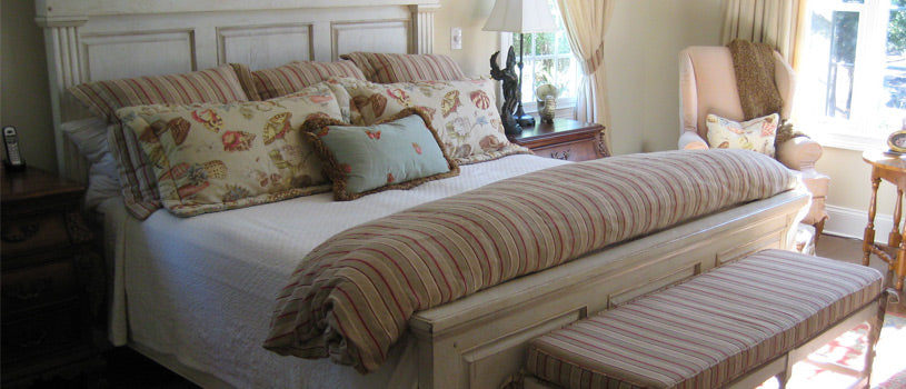 linen bedding on old fashioned bed in carpeted bedroom
