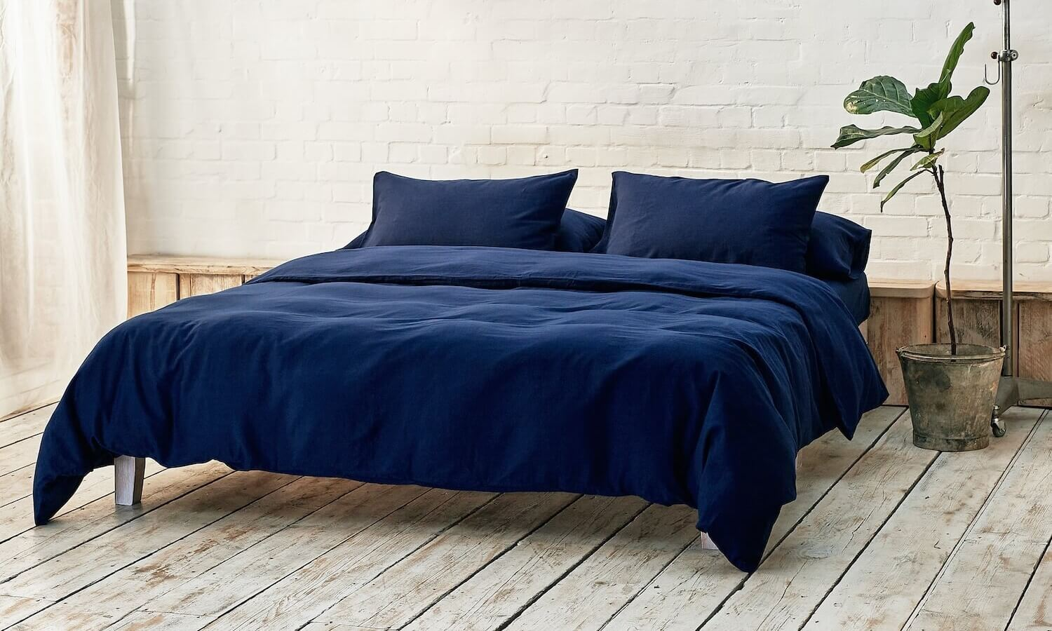 navy blue duvet cover, two pillowcases, and bottom sheet on double bed in apartment with plant and wooden flooring