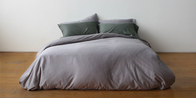 minimalist bedroom with plain grey bedding on bed